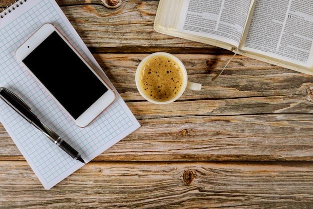 Ochtendstudie met bijbel met zwarte koffiekop op smartphone en pen over spiraalvormige blocnote op hout