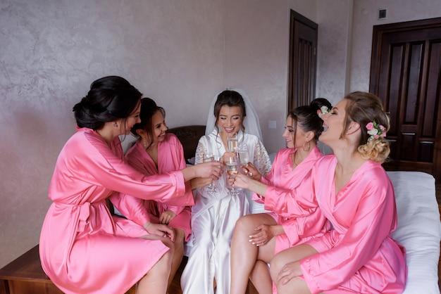 Ochtendtraditie van bruidsmeisjes en bruid met champagne, zijdezachte nachtkleding, feest