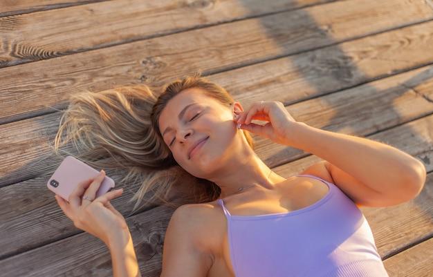 Ochtendtraining. de jonge sportvrouw in sportkleding gebruikt smartphone en listem muziek met oortelefoons terwijl op de strandpijler bij zonsopgang ligt