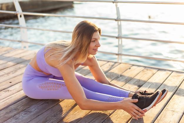Ochtendtraining. opwarmen voor training. jonge geschikte vrouw in sportkleding die been het uitrekken doen zich terwijl het zitten op de strandpijler bij zonsopgang
