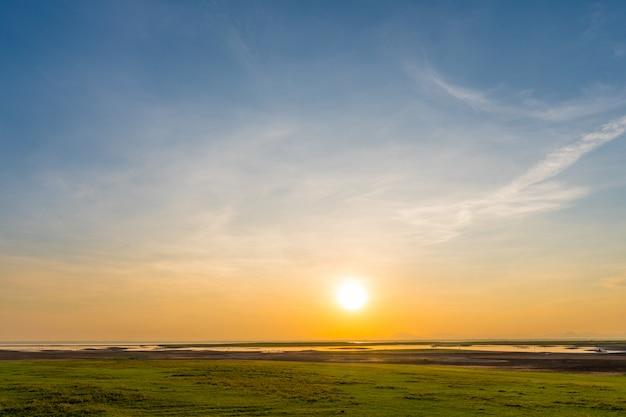 Ochtendzonsopgang door het meer met groen gazon en blauwe hemel