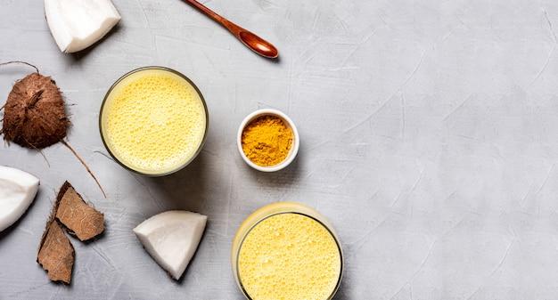 Ocosmelk met kurkuma, specerijen en honing in glazen, kokosnoot en kurkumapoeder op een grijze achtergrond, bovenaanzicht, plat lag.
