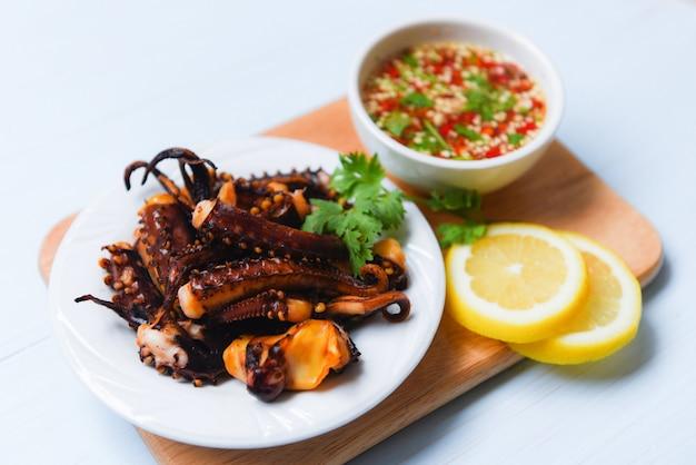 Octopus salade met citroen kruiden en specerijen op witte plaat tentakels inktvis gegrilde voorgerecht eten warme en pittige chili saus zeevruchten