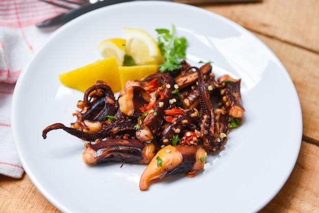 Octopussalade met citroenkruiden en kruiden op witte plaat