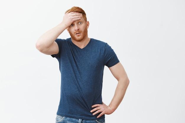 Oef, bijna betrapt. portret van schattige vermoeide man met rood haar die opgelucht aanvoelt, zweet uit het voorhoofd zwaait, opzij kijkt met uitgeputte uitdrukking, alle problemen overwint en uitademt
