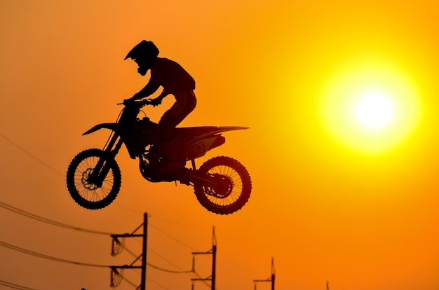 Oefendag, silhouet van een motorfiets motorcross springen op zonsondergang achtergrond.