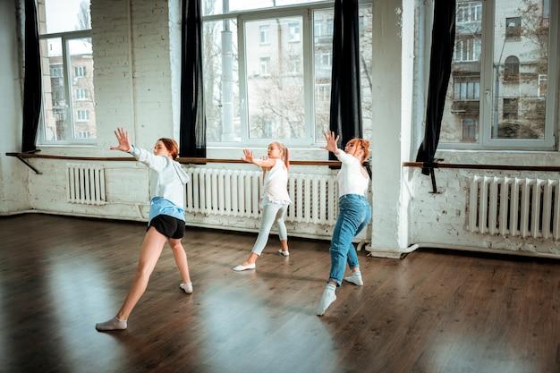 Oefenen. roodharige dansleraar gekleed in een blauwe spijkerbroek en haar studenten trainen in de studio