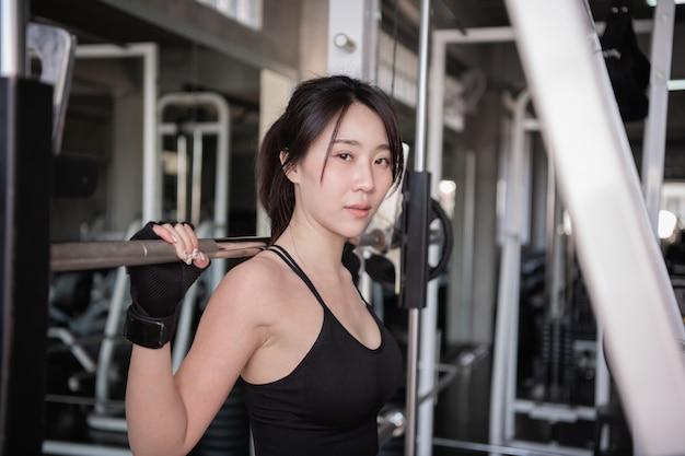 Oefening concept. een mooi meisje oefent in de gymnastiek. mooi goed gevormd meisje omdat zij barbell speelt.