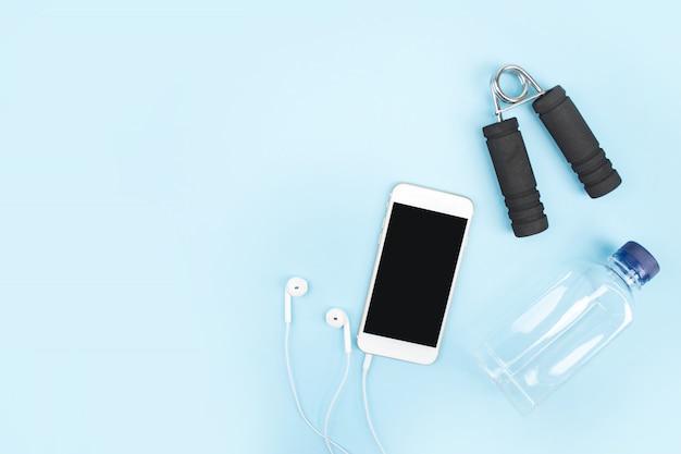 Oefening om gewicht te verliezen met een smartphone, hoofdtelefoons en flessen water op een blauwe achtergrond. met kopie ruimte.