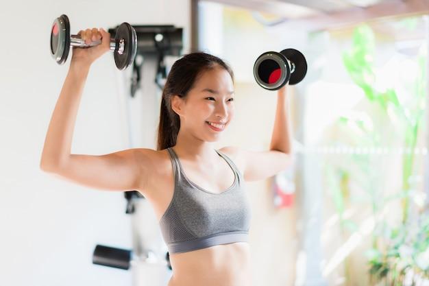 Oefening van de portret de mooie jonge aziatische vrouw met geschiktheidsmateriaal in gymnastiekbinnenland