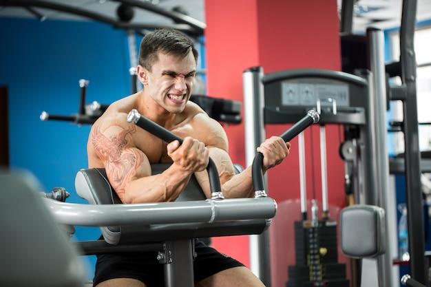 Oefening voor biceps. jonge bodybuilder die zwaargewicht oefening voor bicepsen doen