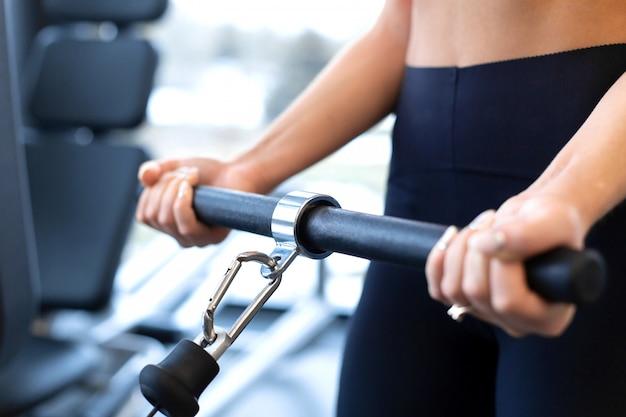 Oefeningen in bloksimulator. biceps-extensie. atletische vrouwentraining in gymnastiek