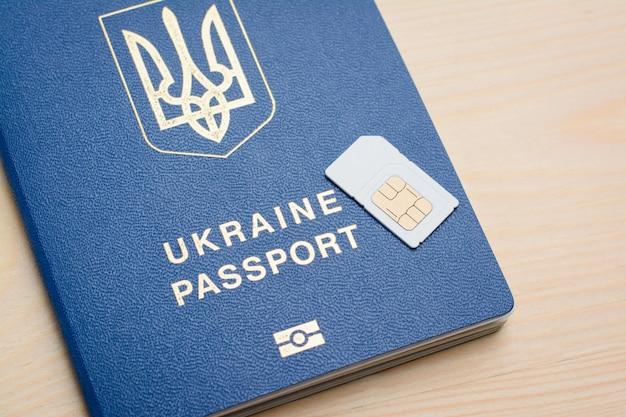 Oekraïens biometrisch paspoort en sim-kaart op hout
