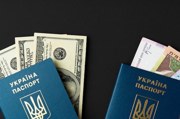 Oekraïens burgerpaspoort met binnen amerikaanse dollars en oekraïense hryvnia bankbiljetten. naar het buitenland gaan, wisselkoersconcept