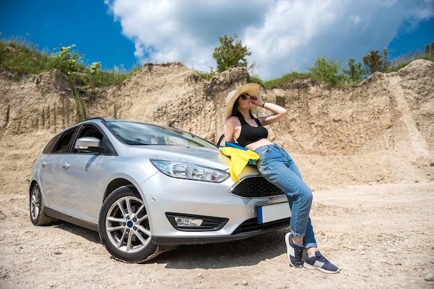 Oekraïens mooi meisje met nationale vlag poseren in een zandgroeve in de buurt van de auto. vrijheid