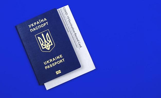 Oekraïens paspoort met covid-19-vaccinatiekaart, vaccinatie in het land op een blauwe achtergrond
