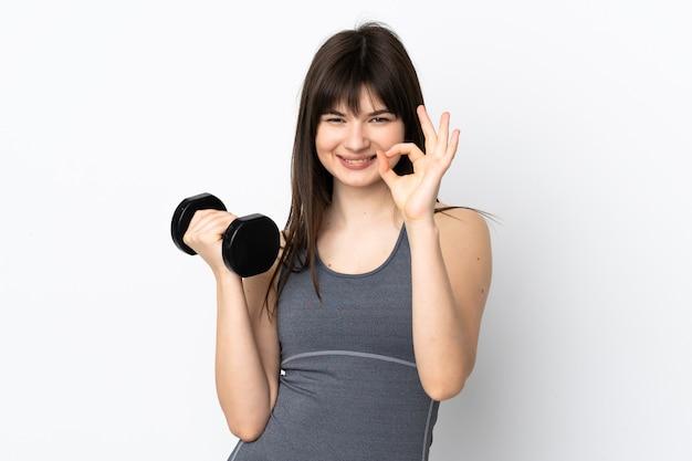 Oekraïens sportmeisje die gewichtheffen maken dat op blauwe muur wordt geïsoleerd die ok teken met vingers toont