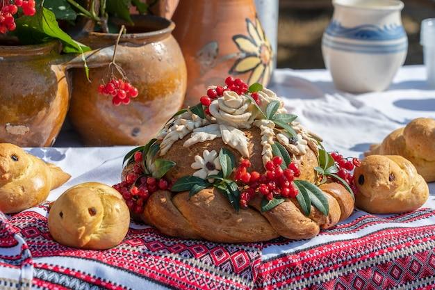 Oekraïens versierd vers brood met zout ligt op tafel, naast de geborduurde handdoek. oekraïense en russische huwelijkstradities. lekkere taart, close-up