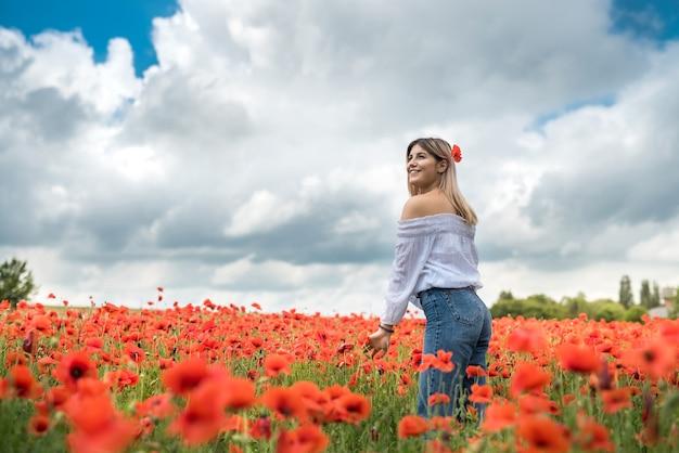 Oekraïense dame die langs een papavergebied loopt