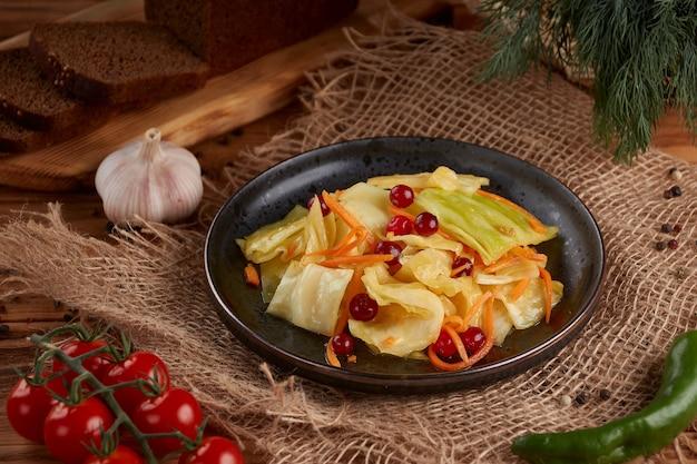 Oekraïense en russische gerechten - zelfgemaakte gemarineerde, zure kool met wortelen en een cranberry in een plaat op de houten