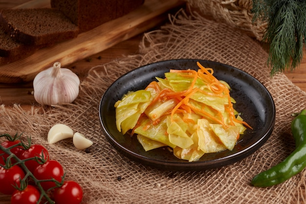 Oekraïense en russische gerechten - zelfgemaakte gemarineerde, zure kool met wortelen in een plaat op houten