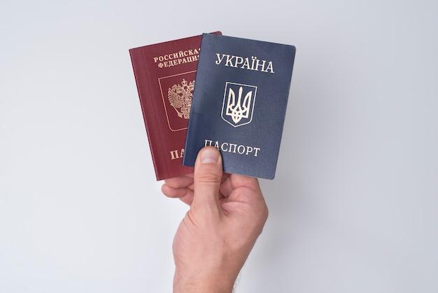 Oekraïense en russische internationale paspoorten in de hand van de man.