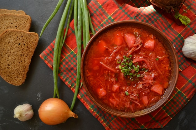 Oekraïense en russische keuken. rode borsjt op een zwarte ondergrond. rood geruit textiel. borsjt met groenten en tomaat. bieten, uien, brood, tomaat, kool, knoflook.