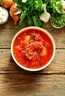Oekraïense en russische keuken, rode borsjt. tomatensoep. groenteborsjt van tomaat, paprika, peterselie, uien, aardappelen, wortelen, kool en bieten. bovenaanzicht