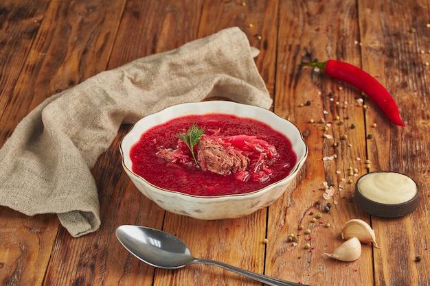 Oekraïense en russische traditionele bietensoep of borsjt in kom met vlees, op houten tafel