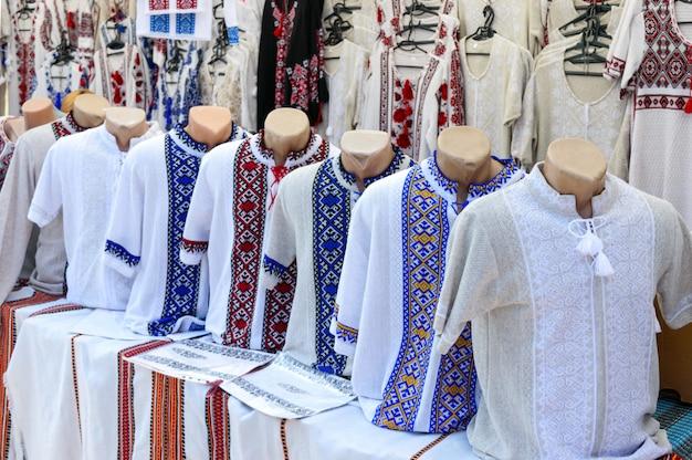 Oekraïense geborduurde shirts, nationale handgemaakte kleding. traditionele linnen overhemd met geborduurde bloemen en ornamenten op de lokale markt op de beurs. fair - een tentoonstelling van volksvakmensen in de open lucht.