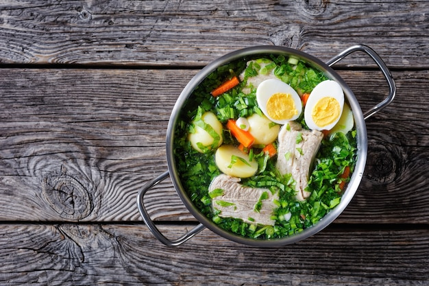 Oekraïense groene zuring soep, peterselie en groene ui met varkensribbetjes, op een vleesbouillon met hardgekookte eierhelften, geserveerd op een metalen bouillonpot op een houten tafel, bovenaanzicht, kopie ruimte