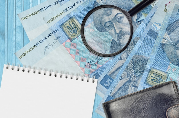 Oekraïense hryvniasrekeningen en vergrootglas met zwarte beurs en blocnote