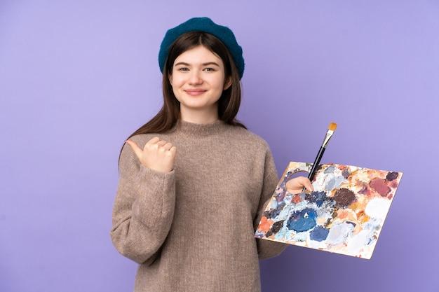 Oekraïense jonge kunstenaarsvrouw die een palet over geïsoleerde purpere muur houdt die aan de kant richt om een product te presenteren