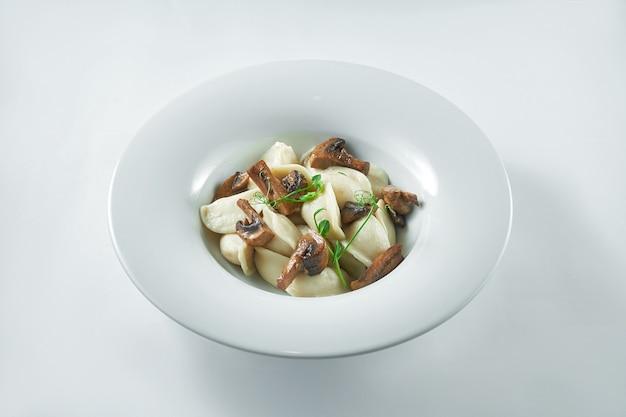 Oekraïense schotel - dumplings met aardappelen en champignons in een witte plaat op een witte plaat. pierogi of varenyky
