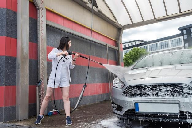 Oekraïense slanke vrouw schoonmaken en wassen schuim haar auto met waterstraal