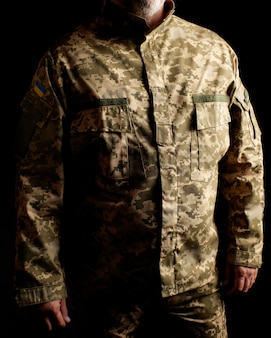 Oekraïense soldaat gekleed in uniform staat in het donker
