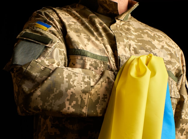Oekraïense soldaat houdt in zijn hand de geelblauwe vlag van de staat, hij drukte zijn hand op zijn borst