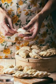 Oekraïense traditionele bakkerijproducten - pierogies maken door vrouwelijke handen. rustieke stijl. retro foto