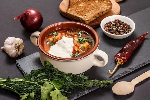 Oekraïense traditionele borsjt in porseleinen kom met roggebrood, peterselie, ui, knoflook en chilipeper op stenen bord. bovenaanzicht.