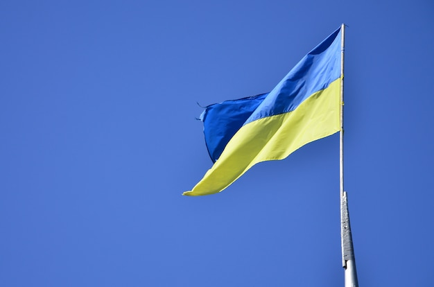 Oekraïense vlag tegen de blauwe wolkenloze hemel
