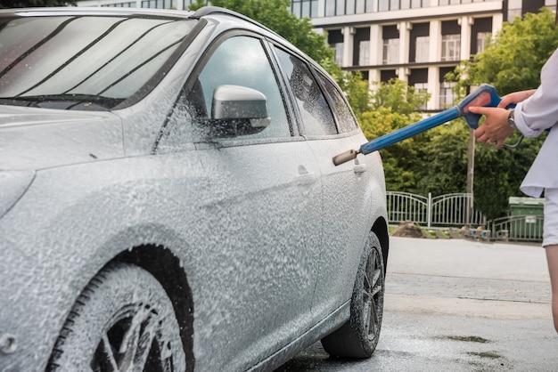 Oekraïense vrouw met schuimwaterpistool reinigt haar auto in dienst. schoonmaak concept