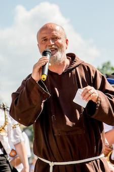 Oekraïne. khmelnytsky regio. juni 2018. preek van de katholieke priester tijdens de vakantie van het gezin. katholieke priester met een vreugdevolle uitdrukking van het gezicht_