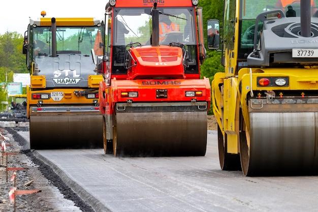 Oekraïne, regio khmelnytsky, krasyliv. mei 2021. walsen voor het leggen van asfalt op de weg tijdens asfaltverdichting. weg reparatie. een nieuwe weg aanleggen