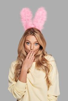 Oeps... aantrekkelijke jonge vrouw in roze konijnenoren die de mond met de hand bedekken en naar de camera kijken terwijl ze tegen een grijze achtergrond staat