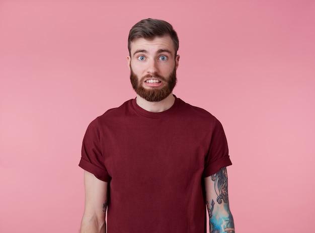 Oeps! er is iets mis! portret van jonge aantrekkelijke getatoeëerde rode bebaarde man in lege t-shirt, ziet er droevig en verdrietig uit, staat over roze achtergrond.