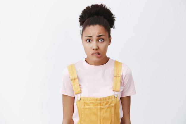 Oeps, ik heb een fout gemaakt door me schuldig te voelen. portret van bezorgde onzekere afro-amerikaanse vrouw met knot kapsel, nerveus lip bijten en starend, sorry willen zeggen over grijze muur