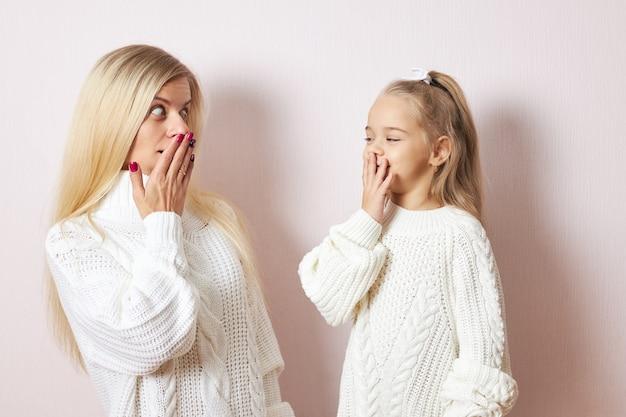 Oeps, omg. schattig klein meisje en haar jonge moeder beide in witte truien poseren geïsoleerd handen op de mond houden, verbaasd zijn over grote verkoopprijzen, gaan winkelen om kerstcadeautjes te kopen