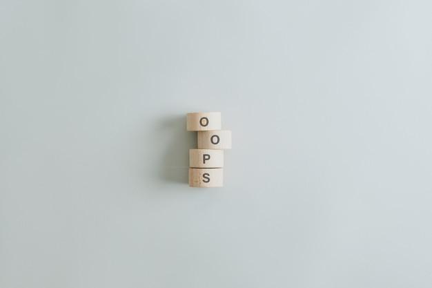 Oeps teken gespeld op gestapelde houten gesneden cirkels op grijs