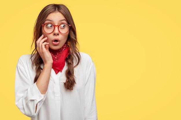 Oeps, zo kan het niet zijn. verbaasde europese vrouw met bril, rode bandana en wit overhemd, kijkt verrassend opzij, houdt de hand op de wang, drukt verbazing uit, modellen tegen gele muur, vrije ruimte