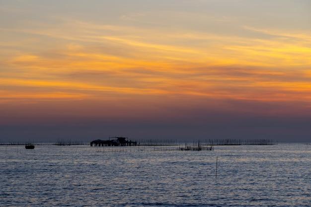 Oesterboerderij in het overzees en de mooie achtergrond van de hemelzonsondergang